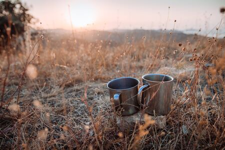 Two metal cups of tea among the grass against the backdrop of the mountains. Concept of autumn hiking trips