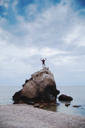 The guy climbed a rock into the sea and raised his arms in a victorious gesture. Zdjęcie Seryjne