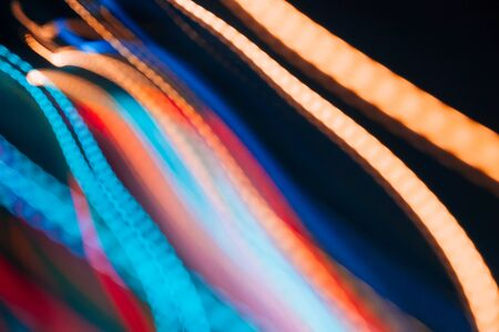 Colorful pattern of red, blue and orange dynamic lines of light. Modern blurred background. Art concept of lighting effects.