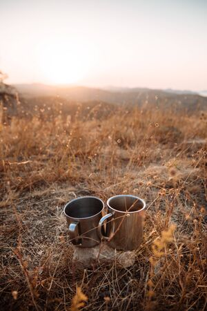 Two metal cups among the grass against the backdrop of the mountains. Concept of autumn hiking trips