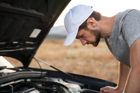 Guy in the white cap opened the hood of the car and looks at the engine. Emergency stop and car repair en route Zdjęcie Seryjne