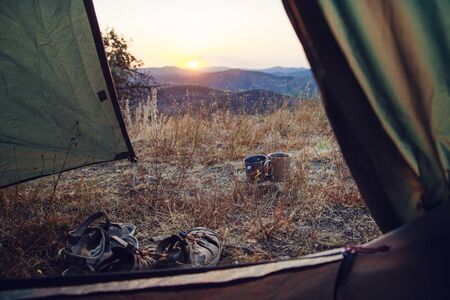 View from the tent: hiking shoes and tea cups against the backdrop of the mountains Zdjęcie Seryjne