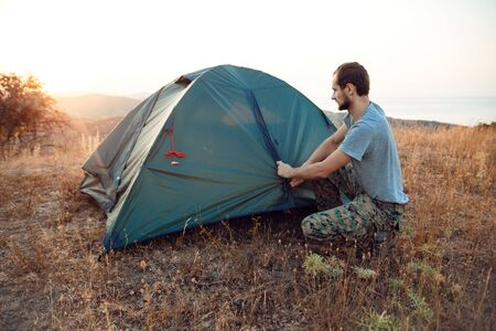 Autumn trekking in the mountains. Tourist sets up a tent Zdjęcie Seryjne
