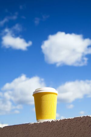 Yellow craft cup of coffee against blue morning sky with clouds. Enjoy, lifestyle, take away breakfast concept.