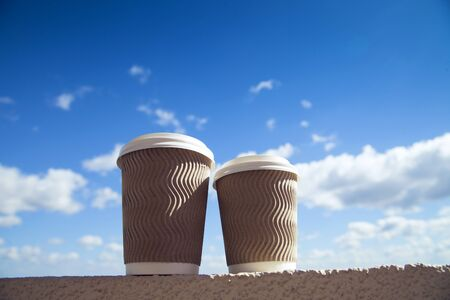 Two craft cups of coffee against blue morning sky with clouds. Enjoy, lifestyle, take away breakfast concept. Zdjęcie Seryjne