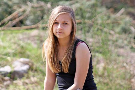 pretty teenage girl sat in woods