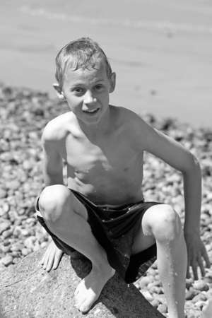 teenage boy sat on a beach photo