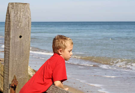 teenage boy looking out to sea Stock Photo