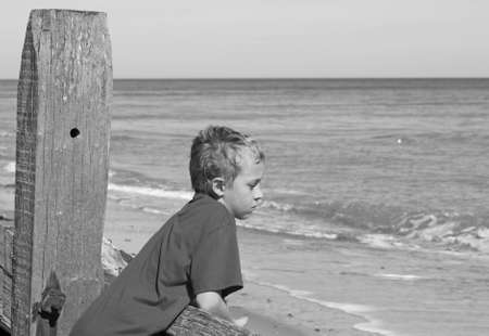 teenage boy looking out to sea photo