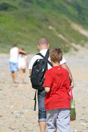 family walking along a beach photo