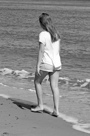 teenage girl walking on a beach photo
