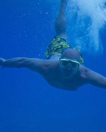 man swimming under water