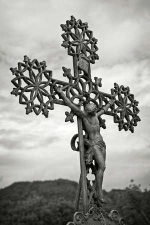 crucify: Old cross against the sky , black and white toned photo
