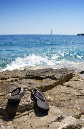 Gone swimming - flipflops on a rocky beach. Summer concept photo