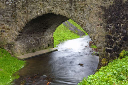 Old stone bridge over a small river in spring time photo