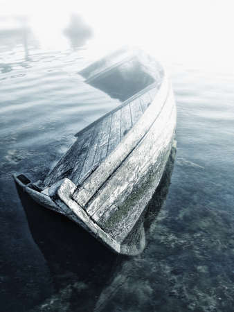 Old abandoned sunken wooden boat in the bay photo