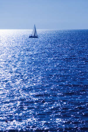 Sailboat on the horizon on a sunny day photo