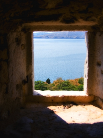 mediaval: Window on an mediaval Mediterranean castle , with view on the bay