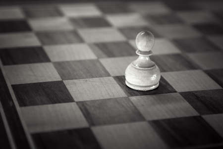 unfair: White pawn down on the chessboard . Black and white retro toned photo with shallow DOF and space for your text Stock Photo