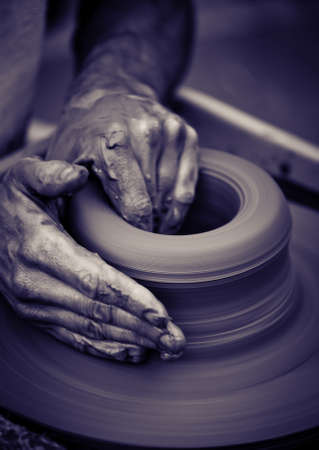 Hands working on pottery wheel , close up retro style toned photo wit shallow DOF photo