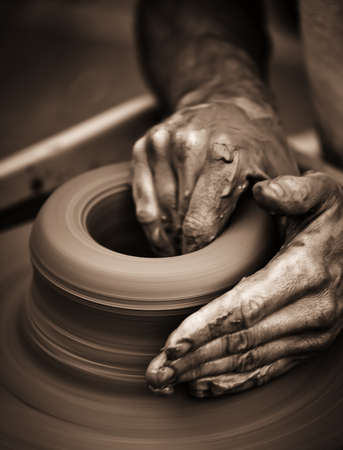 sculptor: Hands working on pottery wheel , close up retro style toned photo wit shallow DOF