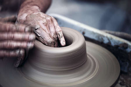 dof: Hands working on pottery wheel , close up retro style toned photo wit shallow DOF