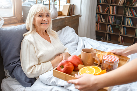Nurse taking care of senior woman breakfast retirement concept