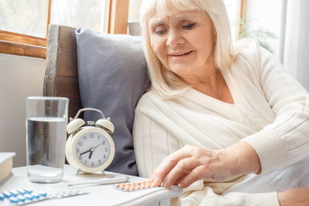 Senior woman resting at home in bed taking pills elderly lifestyle Stock Photo