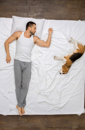 Young man relaxation on the bed top view with a dog