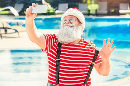 Santa Claus near the pool holiday vacation concept Standard-Bild