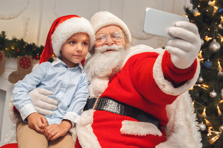 Santa Claus with kids indoors christmas celebration concept Standard-Bild