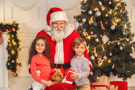 Santa Claus with kids indoors christmas celebration concept Stok Fotoğraf