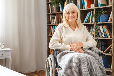 Senior woman with disability recovery at home sitting in a wheelchair covered