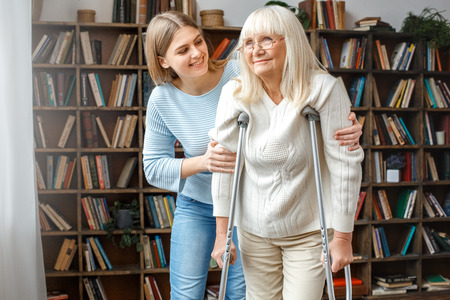 Granddaughter taking care of her retired grandmother with crutches Banque d'images