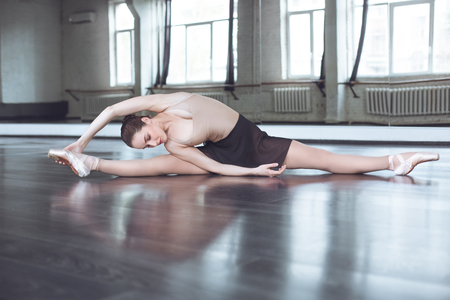 Young ballet dancer practice legs stratching in studio active lifestyle Stock Photo