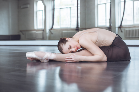 Young ballet dancer practice stratching in studio active lifestyle