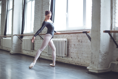 Young ballet dancer practice movement legs stratching in studio active lifestyle Stock Photo