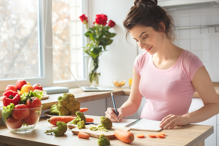 Young pregnant woman in the kitchen at home planning smiling