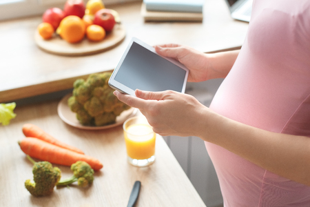 Young pregnant woman in the kitchen at home maternity concept holding digital tablet close-up Stock Photo