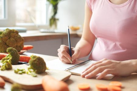 Jonge zwangere vrouw in de keuken die thuis het winkelen lijstclose-up schrijft Stockfoto