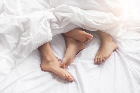 Jong koppel man en vrouw intieme relatie op bed voeten