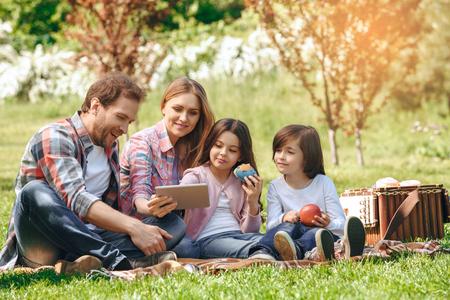 Familie samen in openlucht in de het conceptenpicknick die van het parkweekend het digitale tablet glimlachen gebruiken Stockfoto - 95237818