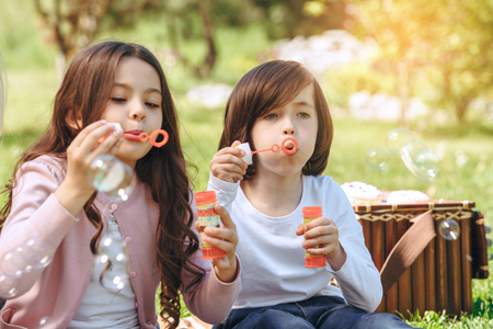 Kids together outdoors in the park weekend concept bubble blower Stockfoto