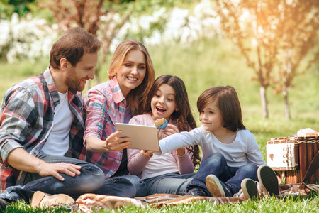Family together outdoors in the park weekend concept picnic browsing internet surprised
