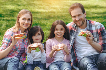 Family together outdoors in the park weekend concept eating sandwiches Stockfoto