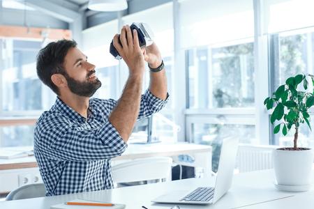 Bedrijfsmens die virtuele werkelijkheidshoofdtelefoon in het kantoor met behulp van Stockfoto - 95466323