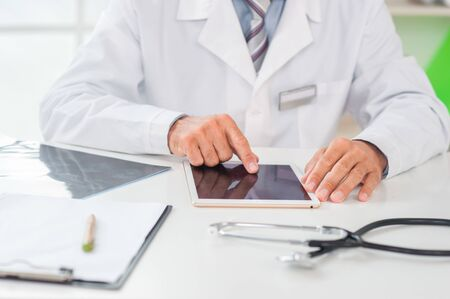 Senior man doctor at his office in clinic close-up sitting browsing digital tablet Stockfoto