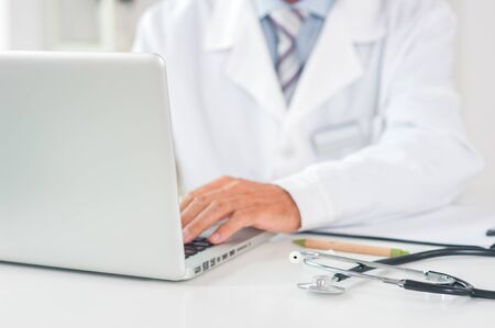 Senior man doctor at his office in clinic close-up sitting using laptop typing front view Stockfoto