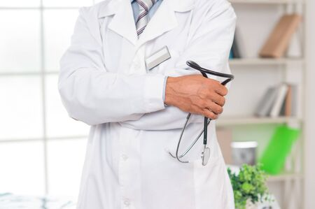 Senior man doctor at his office in clinic close-up standing carry stethoscope