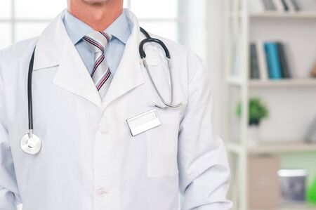 Senior man doctor at his office in clinic close-up standing confident Stockfoto - 131768999